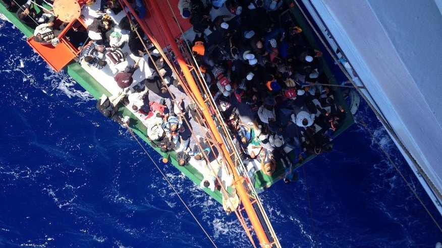 This Sept. 25, 2014 photo taken from a cruise ship that rescued the migrants from a stranded shows migrants on a small boat off the southwestern coast of the east Mediterranean island.  More than 300 people, apparent refugees fleeing from Syria, refused to leave a cruise ship that rescued them from a small boat stranded off Cyprus, a cruise line official said Thursday.  Salamis Cruise Lines Managing Director Kikis Vasiliou said that the people are insisting that they be taken to Italy instead. (AP Photo/Haris Milonas)