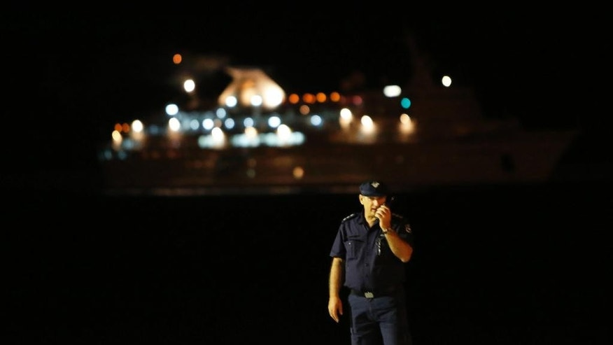 A policeman stands guard as a ship, that picked up some 345 migrants from a small boat stranded off the southwestern coast of Cyprus, arrives at the Mediterranean island's port of Limassol on Thursday, Sept. 25, 2014. The Cypriot Defense Ministry said the 345 people, including 53 children, would arrive at the country's southern port of Limassol. They will then be taken to a reception center near the capital Nicosia where they will be given shelter and medical attention. (AP Photo/Petros Karadjias)
