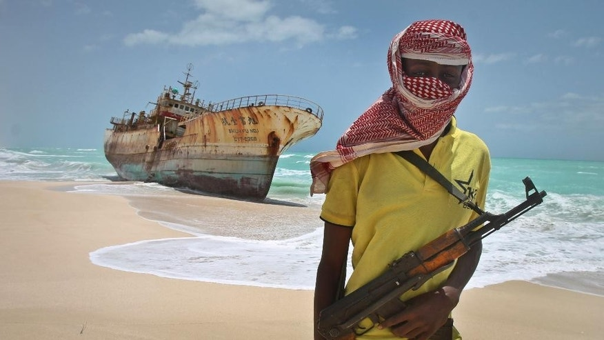 Sept. 23, 2012: In this file photo, masked Somali pirate Hassan stands near a Taiwanese fishing vessel that washed up on shore after the pirates were paid a ransom and released the crew, in the once-bustling pirate den of Hobyo, Somalia. Three Somali pirates were killed in a fight over the ransom paid to free the German-American journalist Michael Scott Moore who was released this week after two years and eight months of captivity, a Somali police official said Friday, Sept. 26, 2014.
