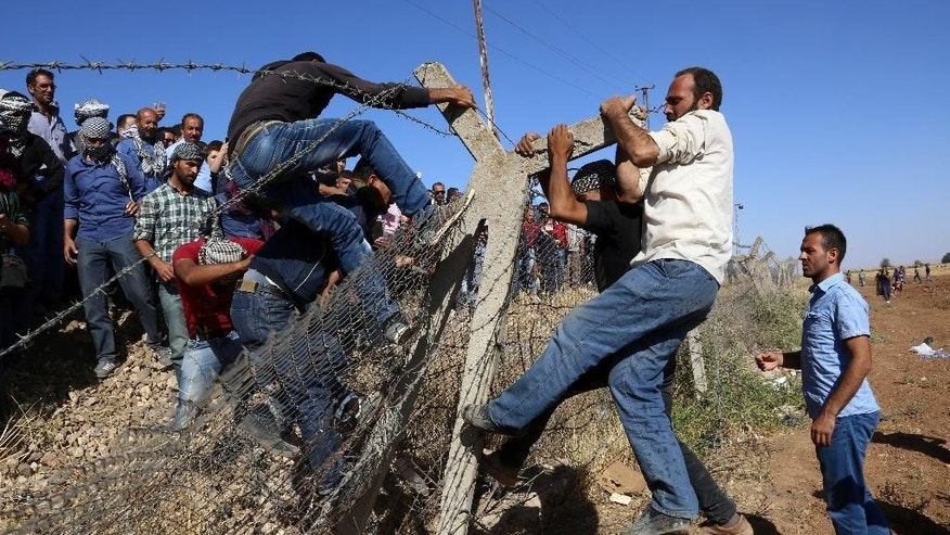 Kurds from Turkey, left, and Syria break down the fences at the Syrian border near Suruc, Turkey, Friday, Sept. 26, 2014. On Thursday, about 1,000 Kurdish activists arrived at the border after a more than 750 mile (1,200 kilometer) overnight bus ride from Istanbul in response to a call for mass mobilization by the imprisoned leader of the PKK rebel group, Abdullah Ocalan.  (AP Photo/Burhan Ozbilici)