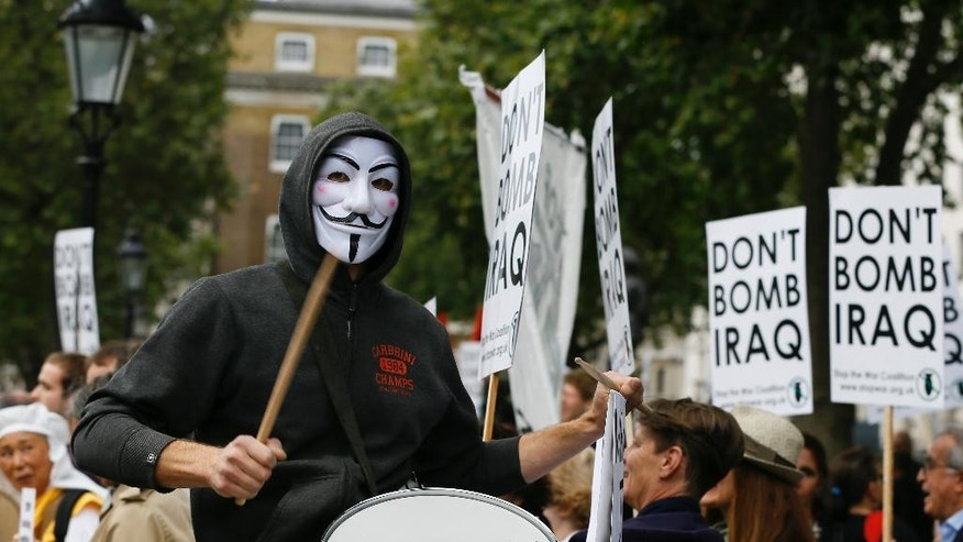 A demonstrator bangs a drum at an anti-war demonstration near Downing Street in London, Thursday, Sept. 25, 2014. The British prime minister said late Wednesday he will ask Parliament to approve joining international airstrikes against the Islamic State group in Iraq. David Cameron announced the move in his address to the U.N. General Assembly. (AP Photo/Kirsty Wigglesworth)