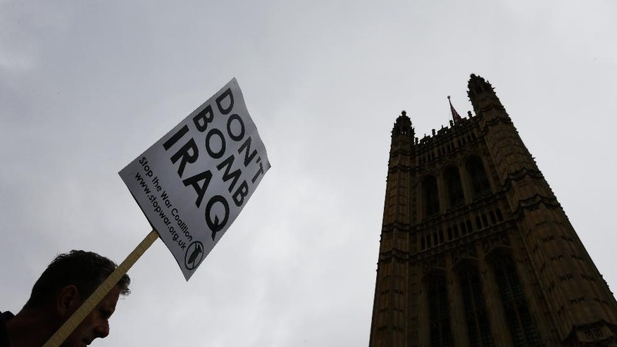A demonstrator holds a banner near Parliament in London, Friday, Sept. 26, 2014. Britain's Parliament is to debate and vote on the UK response to Iraqi's government's request for support against the Islamic State group. A result to the vote is expected late Friday. (AP Photo/Kirsty Wigglesworth)
