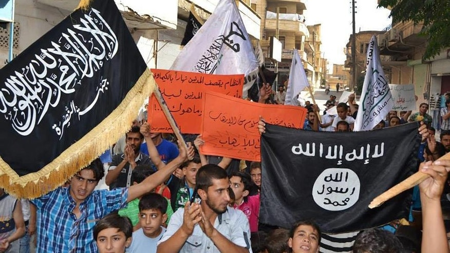 In this photo provided by an anti-Bashar Assad activist group Edlib News Network (ENN), which has been authenticated based on its contents and other AP reporting, anti-Syrian government protesters carry flags of the al-Qaida-affiliated Nusra Front, left, and Islamic State group, right, during a demonstration against the U.S.-led coalition airtstrikes, at Maarat Masrin town, in Idlib province, northern Syria, Friday Sept. 26, 2014. In towns and villages controlled by Syria's mainstream rebel factions, the airstrikes have garnered mixed reactions. Most people appear to condone hitting the Islamic State group, but question why President Bashar Assad's forces which have killed thousands of people in the civil war _ remain untouched. (AP Photo/Edlib News Network ENN)