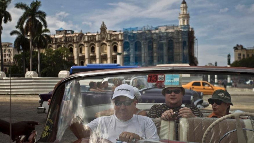 Tourists sit in a classic American car in Old Havana, Cuba, Friday, Sept. 26, 2014. Tourism is one of Cuba's top four generators of income, along with nickel mining, medical services and remittances from relatives living abroad. (AP Photo/Franklin Reyes)
