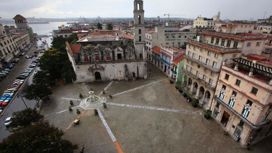 FILE - This Sept. 11, 2013 file photo shows the San Francisco de Asis plaza during a light rain near the harbor in Old Havana, Cuba. Cuba's state-run tourism industry is increasingly doing business with the country's new class of entrepreneurs, trying to improve quality of food and lodging while maintaining a grip on the sector's biggest sources of foreign exchange. (AP Photo/Franklin Reyes, File)