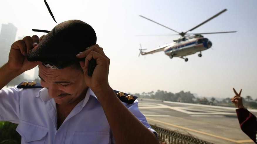 An Egyptian policeman takes cover while a supporter of former Egyptian President Hosni Mubarak gives the victory sign as a helicopter ambulance takes off with Mubarak from the Maadi Military Hospital en route to the Cairo Police Academy for a court appearance in Cairo, Egypt, Saturday, Sept. 27, 2014. The final verdict in the retrial of Mubarak on charges he ordered the killings of hundreds of protesters during the 2011 uprising against his rule will be issued Saturday. Mubarak was found guilty in June 2012 and sentenced to life imprisonment but won a retrial, which began in April 2013. (AP Photo/Hassan Ammar)