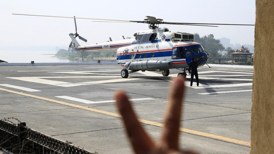 A supporter of former Egyptian President Hosni Mubarak gives the victory sign  as a helicopter ambulance takes off with Mubarak from the Maadi Military Hospital en route to the Cairo Police Academy for a court appearance in Cairo, Egypt, Saturday, Sept. 27, 2014. The final verdict in the retrial of Mubarak on charges he ordered the killings of hundreds of protesters during the 2011 uprising against his rule will be issued Saturday. Mubarak was found guilty in June 2012 and sentenced to life imprisonment but won a retrial, which began in April 2013. (AP Photo/Hassan Ammar)