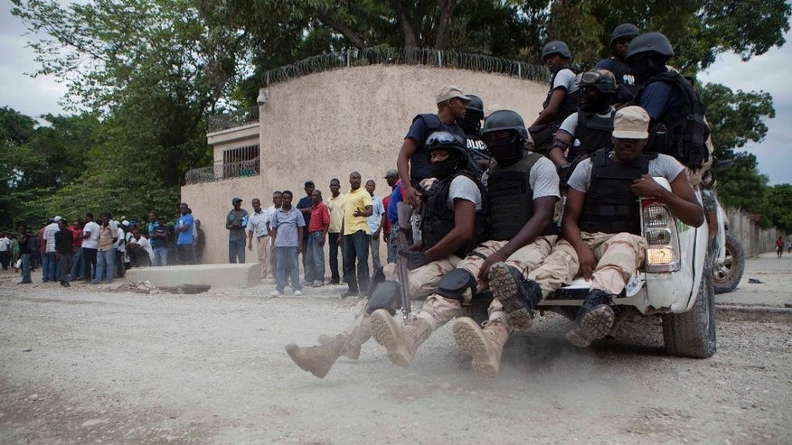 National police officers patrol outside the home of Haiti's former President Jean-Bertrand Aristide in Port-au-Prince, Haiti, Saturday, Sept. 27, 2014. Aristide supporters rallied outside his home Saturday after a new unit of police officers was abruptly posted outside the walled compound in the capital amid fears that the ex-leader faces arrest for failing to heed a court summons. (AP Photo/Dieu Nalio Chery)