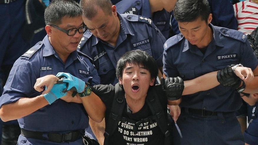 A student is taken away by policemen at the government headquarter  in Hong Kong, Saturday, Sept. 27, 2014. Riot police in Hong Kong on Saturday arrested scores of students who stormed the government headquarters compound during a night of scuffles to protest China's refusal to allow genuine democratic reforms in the semiautonomous region.(AP Photo/Vincent Yu)