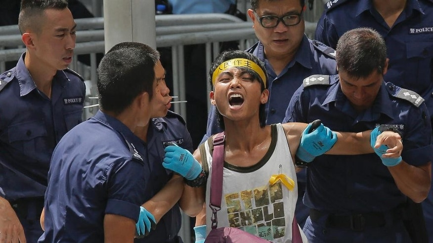A student is taken away by policemen at the government headquarters in Hong Kong, Saturday, Sept. 27, 2014. Riot police in Hong Kong on Saturday arrested scores of students who stormed the government headquarters compound during a night of scuffles to protest China's refusal to allow genuine democratic reforms in the semiautonomous region. (AP Photo/Vincent Yu)