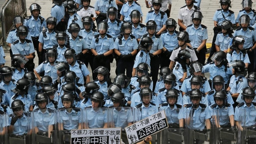 """A protester raises placards that read """"Occupy Central and Citizen Against Order""""  in front of riot policemen outside the government headquarter in Hong Kong, Saturday, Sept. 27, 2014. Riot police in Hong Kong on Saturday arrested scores of students who stormed the government headquarters compound during a night of scuffles to protest China's refusal to allow genuine democratic reforms in the semiautonomous region. (AP Photo/Vincent Yu)"""