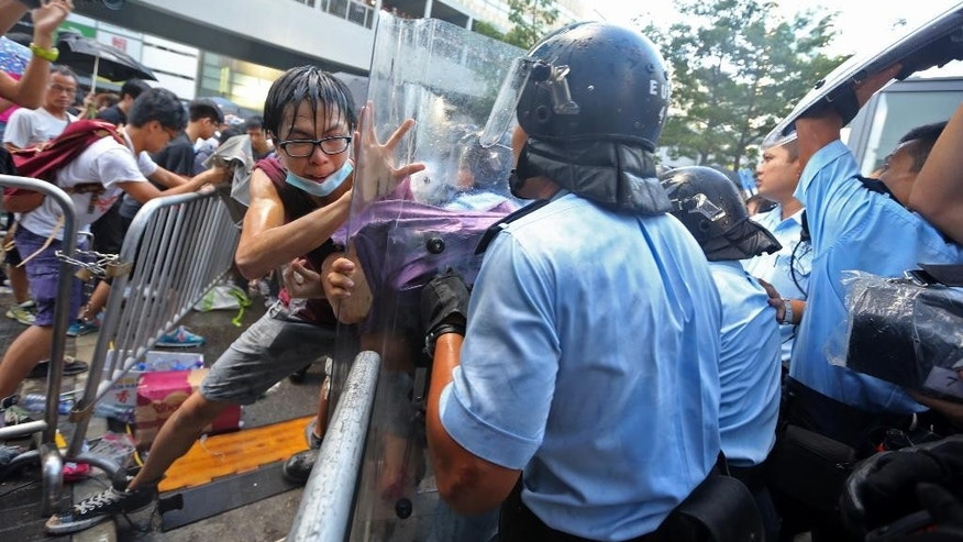 Riot policemen scuffle with protesters after young pro-democracy activists forced their way into Hong Kong government headquarters during a demonstration in Hong Kong, early Saturday, Sept. 27, 2014. The scenes of disorder came at the end of a weeklong strike by students demanding China's communist leaders allow residents to directly elect a leader of their own choosing in 2017. (AP Photo/Apple Daily) HONG KONG OUT, TAIWAN OUT
