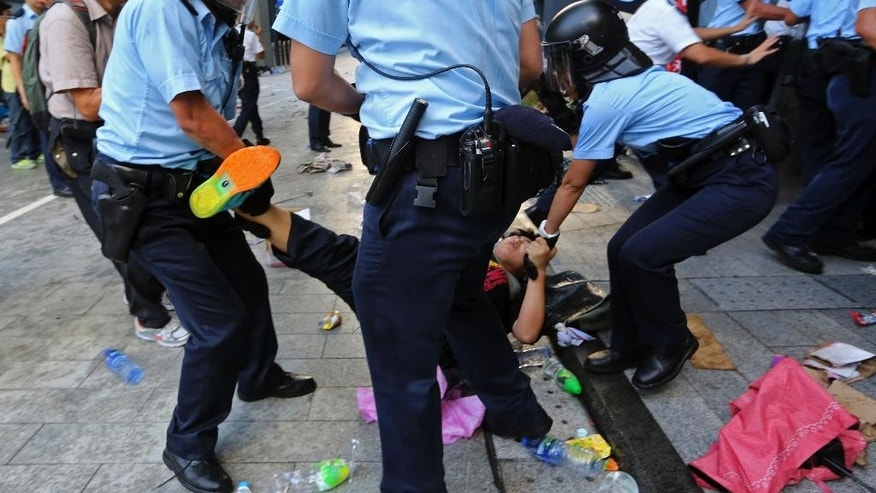 A protester is dragged away by riot policemen after young pro-democracy activists forced their way into Hong Kong government headquarters during a demonstration in Hong Kong, early Saturday, Sept. 27, 2014. The scenes of disorder came at the end of a weeklong strike by students demanding China's communist leaders allow residents to directly elect a leader of their own choosing in 2017. (AP Photo/Apple Daily) HONG KONG OUT, TAIWAN OUT