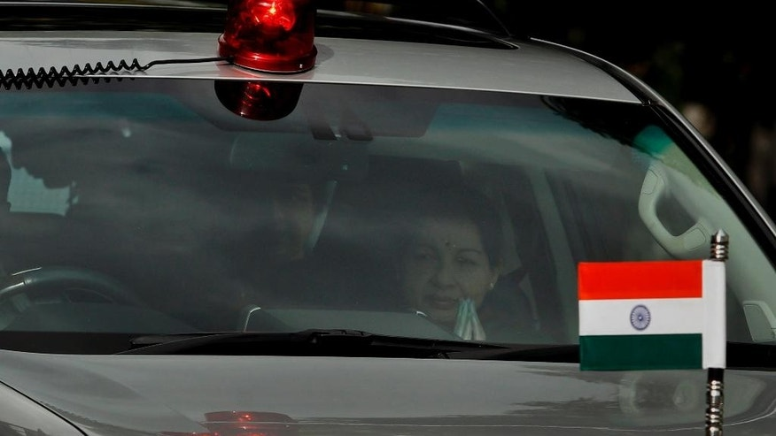 Chief Minister of Tamil Nadu state Jayaram Jayalalitha, right, is seen through the mirror of a car as she comes out of her house in Chennai, India, Saturday, Sep. 27, 2014. A court in southern India has found the top elected official of Tamil Nadu state guilty of corruption in a case filed 18 years ago. Jayalalitha will have to step down as the state chief minister after the court on Saturday found her guilty of possessing wealth disproportionate to her known sources of income. (AP Photo/Arun Sankar K.)