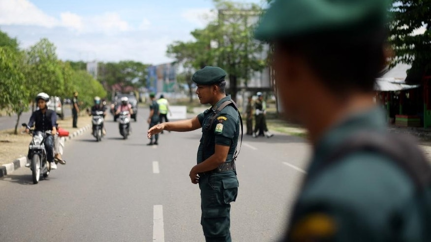 In this Sept. 25, 2014 photo, Islamic sharia police officers stand to check motorists on the street in Aceh province, Indonesia. Lawmakers in Indonesia's conservative Aceh province have passed a law that makes gay sex punishable by caning and subjects non-Muslims to it too. (AP Photo/ Heri Juanda)