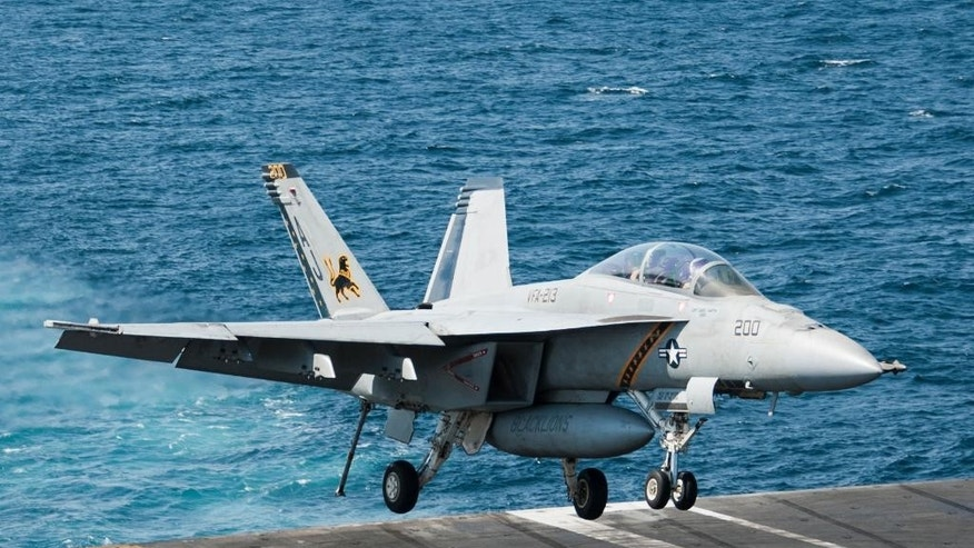 "In this Tuesday, Sept. 23, 2014 photo released by the U.S. Naby, an F/A-18F Super Hornet, attached to the ""Fighting Black Lions"" of Strike Fighter Squadron (VFA) 213 lands aboard the aircraft carrier USS George H.W. Bush, which is supporting U.S.-led coalition airstrikes on Islamic State group and other targets in Syria and Iraq.  Coalition warplanes bombed oil installations and other facilities in territory controlled by Islamic State militants in eastern Syria on Friday, Sept. 26, 2014, taking aim for a second consecutive day at a key source of financing that has swelled the extremist group's coffers, activists said. (AP Photo/U.S. Navy, Brian Stephens)"