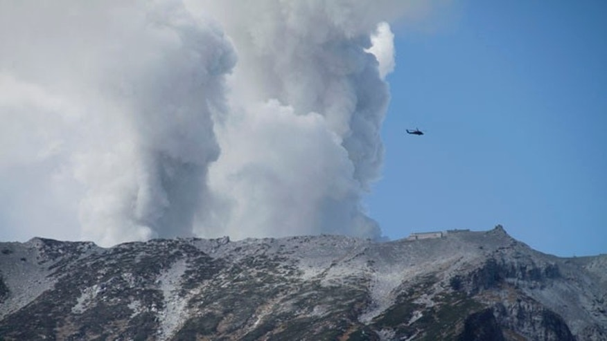 September 28, 2014: A military helicopter, aiding in rescue operations, flies above Mount Ontake as it continues to erupt in Nagano prefecture.