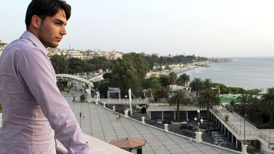 In this June 26, 2014 photo, Riccardo Cordi' stands on a terrace in Reggio Calabria, Sicily, Italy with the Strait of Messina in the background. Cordi' was exiled to Messina during a pioneering anti-mafia program for juveniles, a kind of rehab away from the mob. (AP Photo/Adriana Sapone)