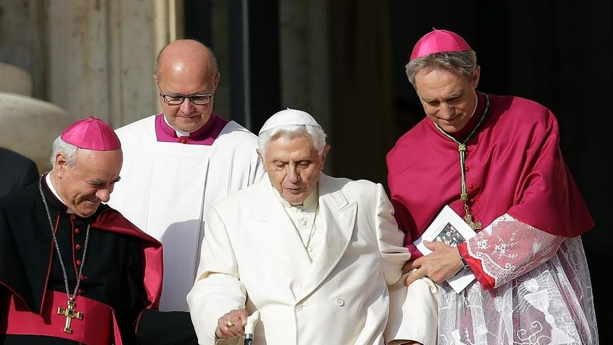 Sept. 28, 2014: Pope Emeritus Benedict XVI, center, is helped to walk down the steps by Bishops Vincenzo Paglia, left, and Georg Gaenswein prior to the start of a meeting of Pope Francis with elderly in St. Peter's Square at the Vatican. (AP)