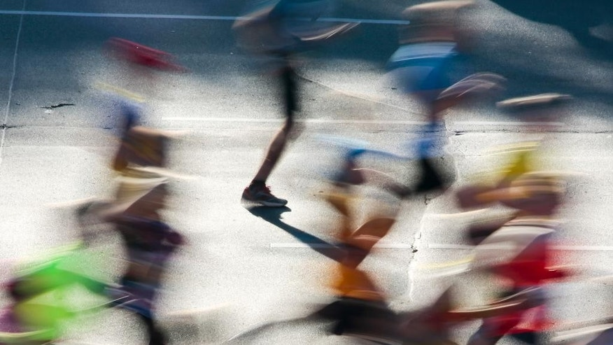 In this photo taken with a long time exposure, runners start the 41st Berlin Marathon in Berlin, Germany, Sunday, Sept. 28, 2014. (AP Photo/Markus Schreiber)