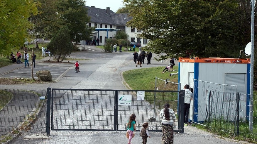People walk in front of the entrance of the refugee camp in Burbach, Germany, Sunday Sept.28,2014.  Police are investigating accusations that guards at an asylum center in Burbach in western Germany repeatedly abused refugees physically and mentally. A police spokesman from Hagen near Burbach said Sunday that police raided the center and questioned both security guards and refugees after a local journalist received a DVD showing the abuse of an asylum seeker by guards. (AP Photo/dpa/Federico Gambarini)