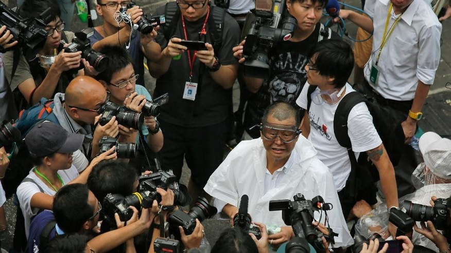 Media mogul Jimmy Lai wearing goggles appears outside the government headquarters to join a protest in Hong Kong, Sunday, Sept. 28, 2014. Hong Kong activists kicked off a long-threatened mass civil disobedience protest Sunday to challenge Beijing over restrictions on voting reforms, escalating the battle for democracy in the former British colony after police arrested dozens of student demonstrators. (AP Photo/Vincent Yu)