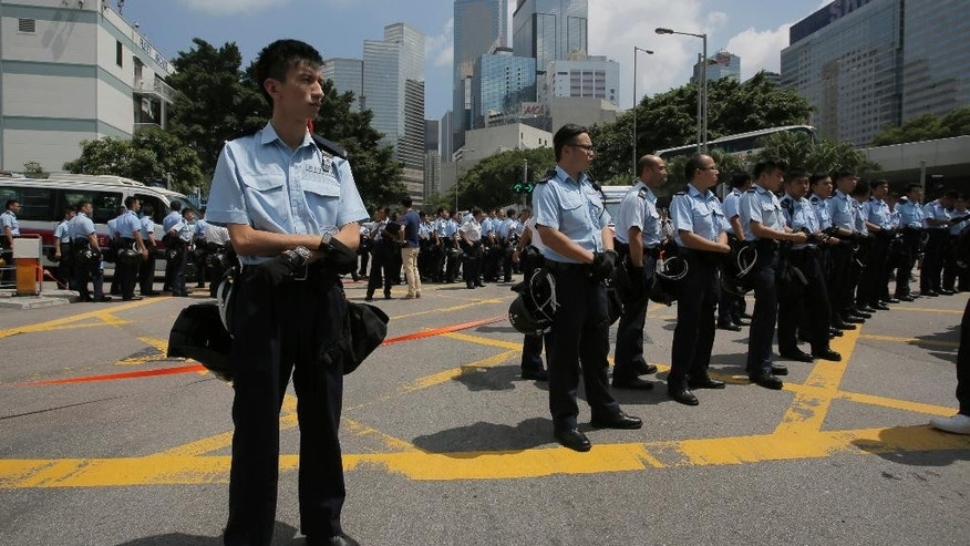 Police officers stand guard the streets surrounding the government headquarters in Hong Kong, Sunday, Sept. 28, 2014. Hong Kong activists kicked off a long-threatened mass civil disobedience protest Sunday to challenge Beijing over restrictions on voting reforms, escalating the battle for democracy in the former British colony after police arrested dozens of student demonstrators. (AP Photo/Vincent Yu)