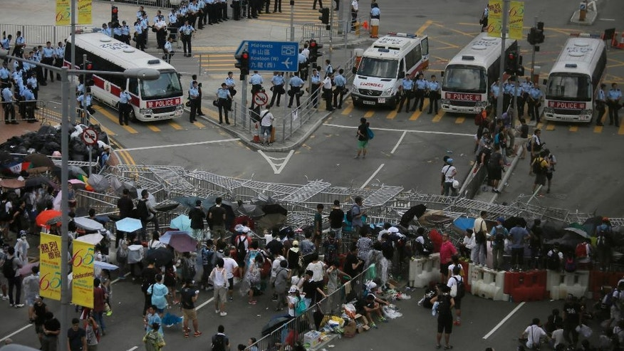 Protesters gather behind barricades used to occupy the streets surrounding the government headquarters in Hong Kong, Sunday, Sept. 28, 2014. Hong Kong activists kicked off a long-threatened mass civil disobedience protest Sunday to challenge Beijing over restrictions on voting reforms, escalating the battle for democracy in the former British colony after police arrested dozens of student demonstrators. (AP Photo/Vincent Yu)