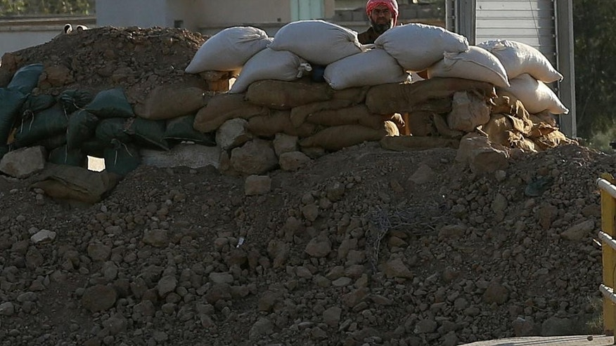 Militant with the Islamic State group peers from behind a barricade at a Kurdish peshmerga position near the Mullah Abdullah Bridge, located on the road between Irbil and Kirkuk, 290 kilometers (180 miles) north of Baghdad, Iraq, Saturday, Sept. 27, 2014. Over a wall of dirt bags across the Mullah Abdullah Bridge in northern Iraq, a militant with the Islamic State group looks at Kurdish fighters stationed on the other side of the bridge. (AP Photo/Hadi Mizban)
