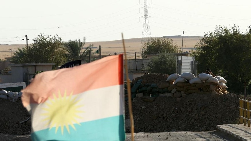 A Kurdish flag blows in the wind in front of a militant with the Islamic State group looking from behind a barricade at a Kurdish peshmerga position near the Mullah Abdullah Bridge, located on the road between Irbil and Kirkuk, 290 kilometers (180 miles) north of Baghdad, Iraq, Saturday, Sept. 27, 2014. Over a wall of dirt bags across the Mullah Abdullah Bridge in northern Iraq, a militant with the Islamic State group looks at Kurdish fighters stationed on the other side of the bridge.  (AP Photo/Hadi Mizban)