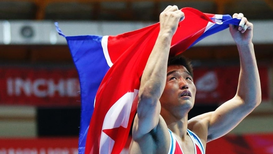 North Korea's Jong Hak-jin runs with his national flag after winning gold in the men's freestyle 57kg contest at the 17th Asian Games in Incheon, South Korea, Saturday, Sept. 27, 2014.  (AP Photo/Kin Cheung)
