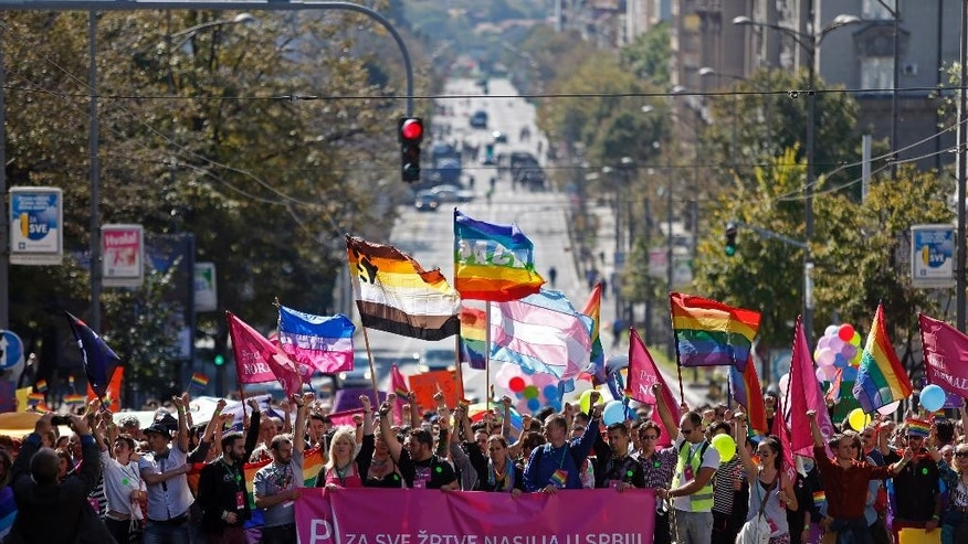 "Gay activists wave flags during the Pride March in Belgrade, Serbia, Sunday, Sept. 28, 2014. Waving hundreds of rainbow-colored flags, several hundred gay activists marched from the government headquarters through the empty Belgrade streets where shops were closed and public transport was stopped. Sign reads ""For all the victims of violence in Serbia"". (AP Photo/Marko Drobnjakovic)"