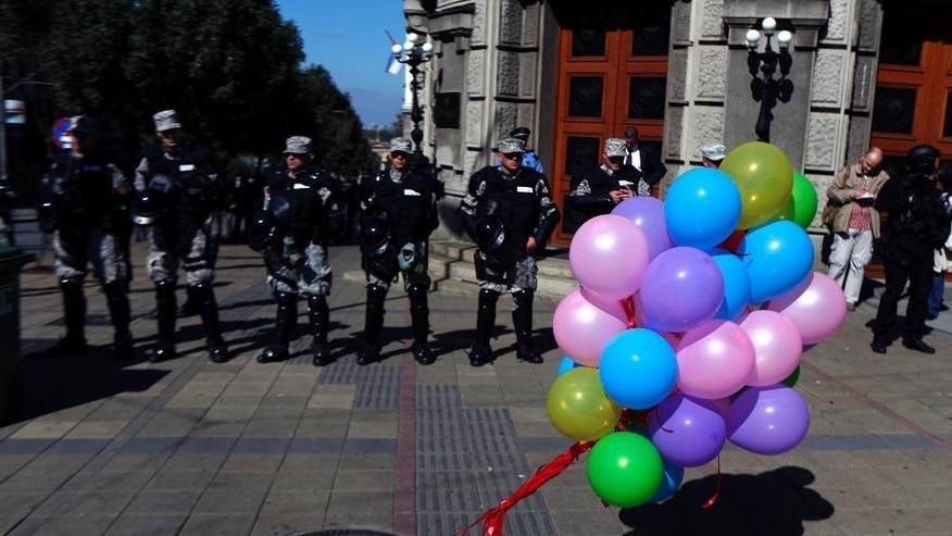 A string of balloons stands in front of members of the Serbian Gendarmerie deployed to protect the Pride March in Belgrade, Serbia, Sunday, Sept. 28, 2014. Thousands of anti-riot police officers were deployed Sunday in downtown Belgrade in an effort to protect a gay pride march that faced threats of attacks from extremists. (AP Photo/Marko Drobnjakovic)