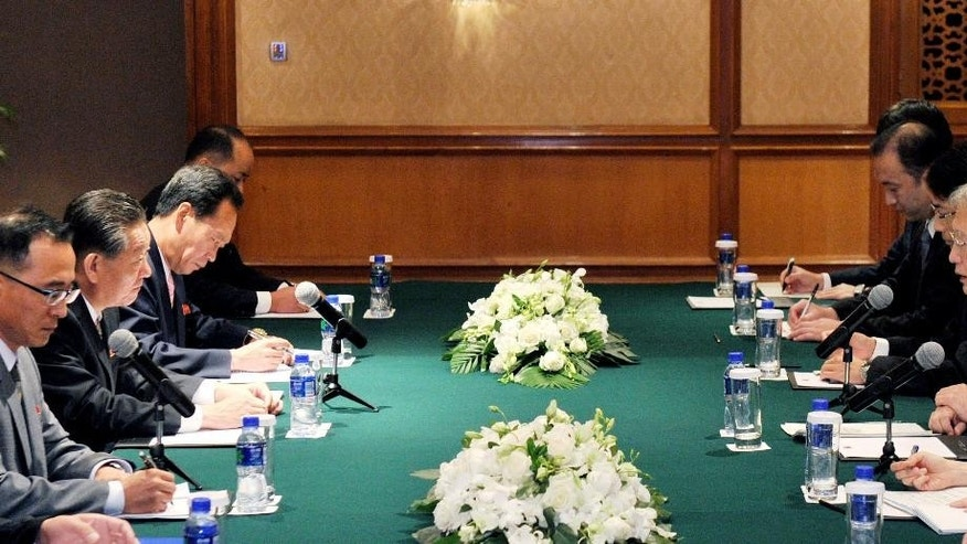 Junichi Ihara, right, head of the Japanese Foreign Ministry's Asia and Oceania Affairs Bureau, left, speaks to Song Il Ho, second left, North Korea's ambassador in charge of normalizing relations with Japan, during their meeting in Shenyang in northeastern China's Liaoning Province, Monday, Sept. 29, 2014. The Monday meeting by negotiators from North Korea and Japan for talks on the abduction of Japanese citizens by North Korean agents was expected to last only one day, with Japan expected to pressure the North Korean delegation to produce a preliminary report on the issue. (AP Photo/Kyodo News, Kenzaburo Fukuhara)
