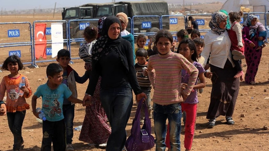 Syrian refugees, mostly Kurds from Kobani, arrive at the Turkey-Syria border near Suruc, Turkey, Saturday, Sept. 27, 2014. (AP Photo/Burhan Ozbilici)