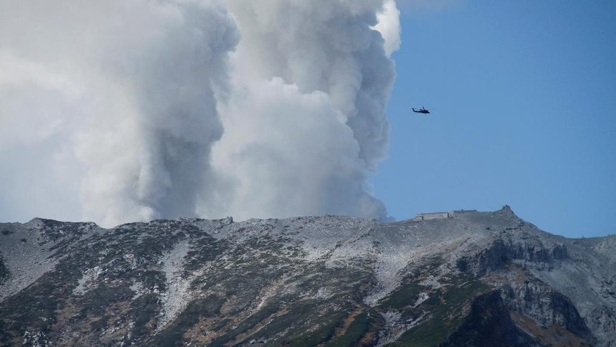 A military helicopter, aiding in rescue operations, flies above Mount Ontake as it continues to erupt, Sunday, Sept. 28, 2014, in Nagano prefecture. Military helicopters plucked several people from the Japanese mountainside Sunday after a spectacular volcanic eruption sent officials scrambling to reach many more injured and stranded on the mountain. Mount Ontake erupted shortly before noon Saturday, catching mountain climbers by surprise and injuring at least 34, including 12 seriously, according to Japan's Fire and Disaster Management Agency. The tally was lower than reported by local officials earlier, but the disaster agency warned that the numbers could still change. (AP Photo/Koji Ueda)
