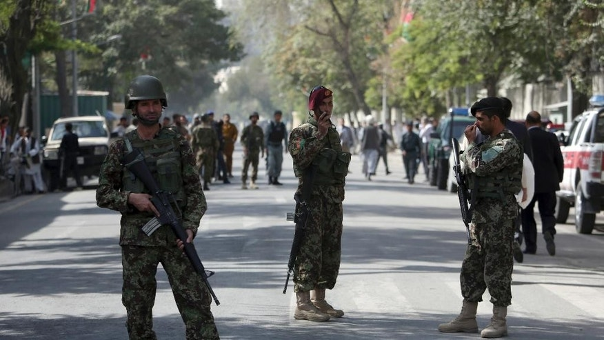 Afghanistan's National Army (ANA) soldiers stand guard at the site of an explosion on a road to the presidential palace, in Kabul, Afghanistan, Sunday, Sept. 28, 2014. A military vehicle was detonated by a bomb in diplomatic area in Kabul city. The explosion occurred in the road to the Afghanistan's president palace, a day before the inauguration for the country's new president. (AP Photo/Rahmat Gul)