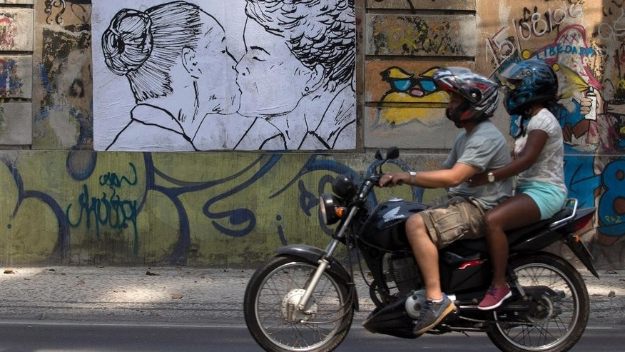 A couple riding a motorcycle, pass in front of a drawing depicting Brazil's President Dilma Rousseff, and rival candidate Marina Silva kissing each other, made by artist Cela Luz, in Rio de Janeiro, Brazil, Monday, Sept. 29, 2014. Brazil will hold general elections on Oct. 5. (AP Photo/Silvia Izquierdo)