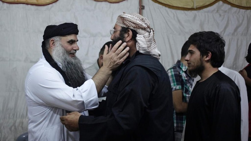 In this Wednesday, Sept. 24, 2014 photo, radical al-Qaida-linked preacher Abu Qatada, first left, receives a friend, on the day he was released from Jordanian prison after an acquittal on security charges, in Amman, Jordan. Abu Qatada and Abu Mohammed al-Maqdisi, two of Jordan's top pro-al-Qaida ideologues held court on the rooftop of a villa whispering to each other and rising occasionally from plastic chairs to greet supporters. The two have denounced some of the Islamic State group's practices as un-Islamic - comments some analysts say have turned the preachers into assets in Jordan's campaign to contain the Islamic State, which is believed to have attracted thousands of followers in Jordan. (AP photo/Mohammad Hannon)
