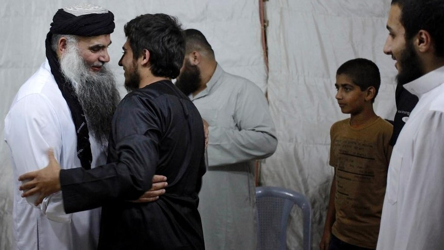 In this Wednesday, Sept. 24, 2014 photo, radical al-Qaida-linked preacher Abu Qatada, left, receives an admirer, on the day he was released from Jordanian prison after an acquittal on security charges, in Amman, Jordan. Abu Qatada and Abu Mohammed al-Maqdisi, two of Jordan's top pro-al-Qaida ideologues held court on the rooftop of a villa whispering to each other and rising occasionally from plastic chairs to greet supporters. The two have denounced some of the Islamic State group's practices as un-Islamic - comments some analysts say have turned the preachers into assets in Jordan's campaign to contain the Islamic State, which is believed to have attracted thousands of followers in Jordan. (AP photo/Mohammad Hannon)