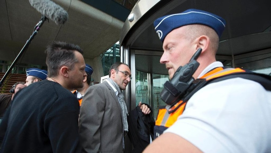 Lawyer Ergun Top, center, arrives at the main courthouse in Antwerp, Belgium on Monday, Sept. 29, 2014. Dozens of Belgians on Monday are going on trial accused of leading or being members of a terrorist organization that allegedly recruited fighters for jihadi groups in Syria. (AP Photo/Virginia Mayo)