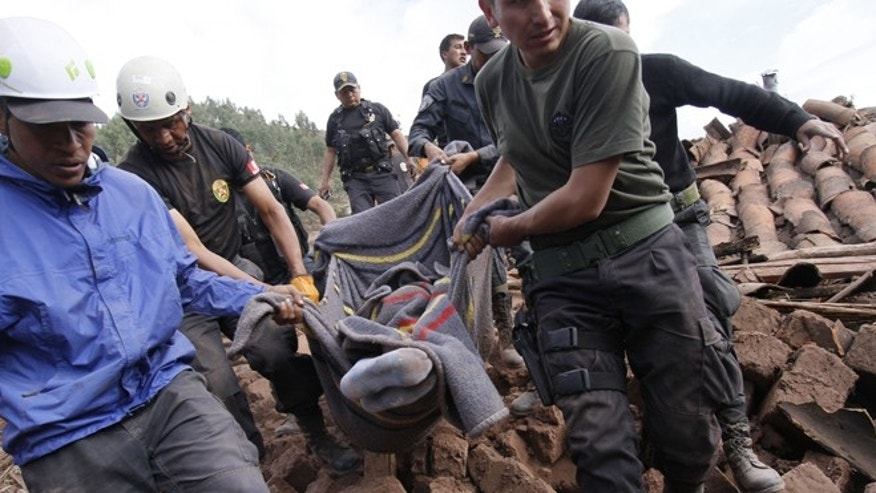 Rescue workers carry a body from the the ruins of a collapsed house after a 4.9 magnitude earthquake shook a remote Andean village near the city of Cuzco, Peru, Sunday Sept 28, 2014. The moderate quake centered just 5 miles underground killed at least 8 people and destroyed several homes that left dozens homeless as well as knocking out power in the village. (AP Photo)
