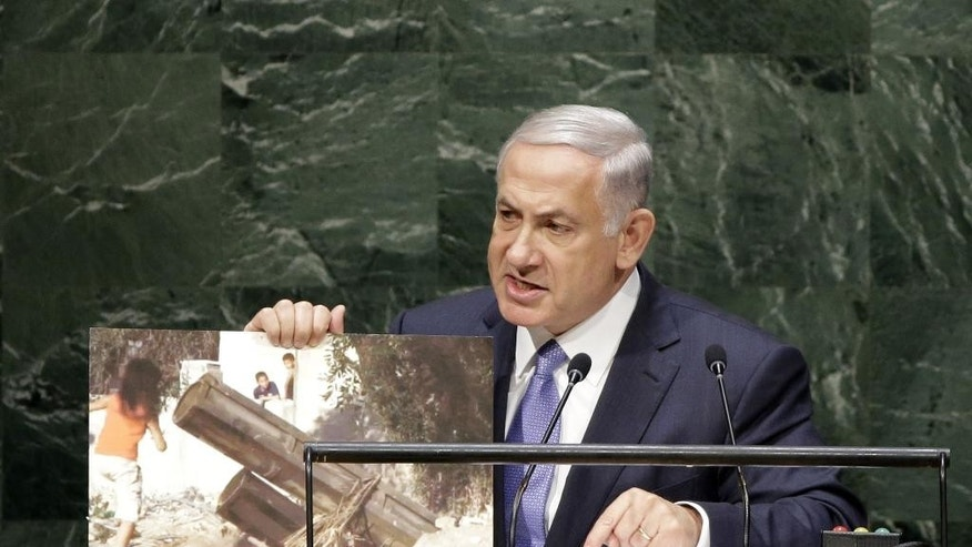 Benjamin Netanyahu, Prime Minister of Israel, holds up a picture of an alleged Hamas rocket launcher surrounded by children while speaking during the 69th session of the United Nations General Assembly at U.N. headquarters, Monday, Sept. 29, 2014. (AP Photo/Seth Wenig)