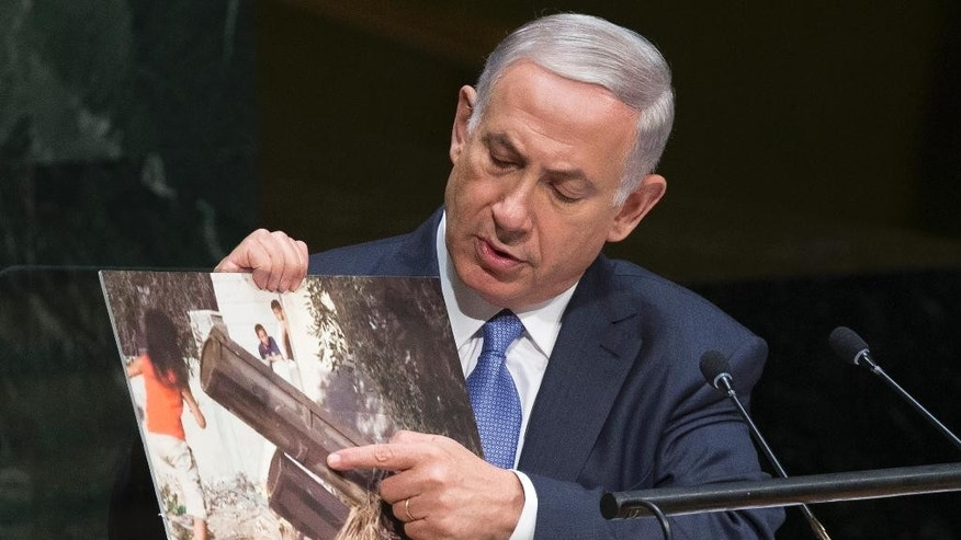 Israel's Prime Minister Benjamin Netanyahu points to a photo he says shows rocket launchers placed in residential neighborhoods of Gaza, as he addresses the 69th session of the United Nations General Assembly at U.N. headquarters, Monday, Sept. 29, 2014. (AP Photo/John Minchillo)