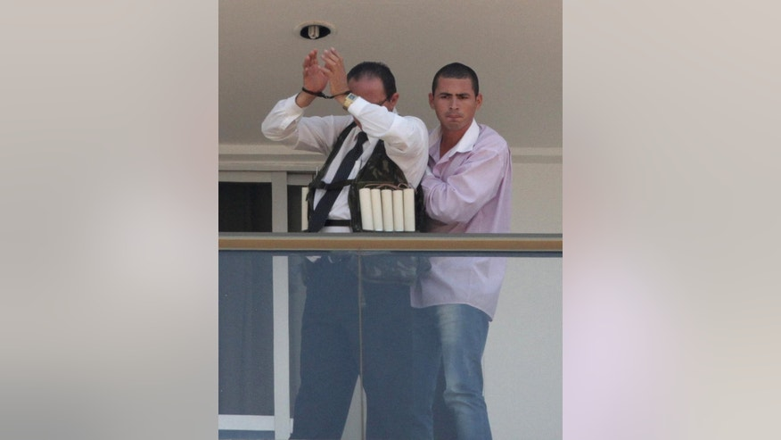 An unidentified man parades a handcuffed hostage wearing what appears to be an explosive vest, on the 13th floor  balcony of the Saint Peter Hotel, in Brasilia, Brazil, Monday, Sept. 29, 2014. Firefighters and police have cordoned off the area and about 300 guests and other employees left the hotel, some reportedly told to leave by the same man carrying out the attack. Police didn't confirm whether there were actually explosives in the garment. (AP Photo/Eraldo Peres)