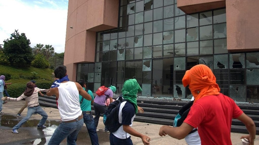 Students from a rural teachers college throw rocks at the entrance to the State Congress after marching through the streets of Chilpancingo, Mexico, Monday Sept. 29, 2014. The students were protesting after a violent weekend left at least 6 people dead and 57 students reported missing. State authorities have confirmed that 22 local policemen have been arrested following the deaths. (AP Photo/Alejandrino Gonzalez)