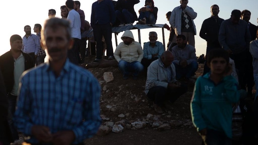 Turkish Kurds watch clashes between Syrian Kurdish fighters and militants of the Islamic State close to Turkey-Syria border near Suruc, Turkey, Sunday, Sept. 28, 2014. (AP Photo)