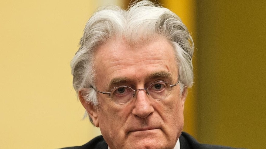 FILE - A Thursday, July 11, 2013 photo from files showing former Bosnian Serb leader Radovan Karadzic awaiting the start of his appeal at the courtroom of the U.N. Yugoslav war crimes tribunal (ICTY) in The Hague, Netherlands. Prosecutors called former Bosnian Serb political leader Radovan Karadzic a liar in closing remarks at his genocide trial, saying his denials of responsibility for atrocities committed on a massive scale while he was in charge lack any credibility. Prosecutor Alan Tieger said Karadzic, 69, should be imprisoned for life if found guilty. Karadzic says he is innocent of any wrongdoing and was unaware of the 1995 slaughter of more than 7,000 Muslim men and boys by Serb forces at Srebrenica, the worst massacre in Europe since World War II. (AP Photo/Michael Kooren, Pool, File)