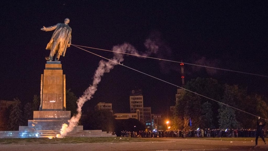 Activists dismantle Ukraine's biggest monument to Lenin at a pro-Ukrainian rally in the central square of the eastern city of Kharkiv, Ukraine, Sunday, Sept. 28, 2014. (AP Photo/Igor Chekachkov)