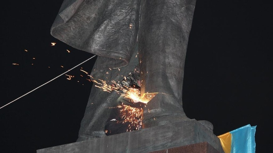An activist dismantles Ukraine's biggest monument to Lenin at a pro-Ukrainian rally  in the central square of the eastern city of Kharkiv, Ukraine, Sunday, Sept.28, 2014. (AP Photo/Sergey Kozlov)